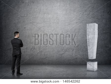 Back view of businessman touching big 3D concrete exclamation mark. Economy and finance. Money and profit. Successful lifestyle.