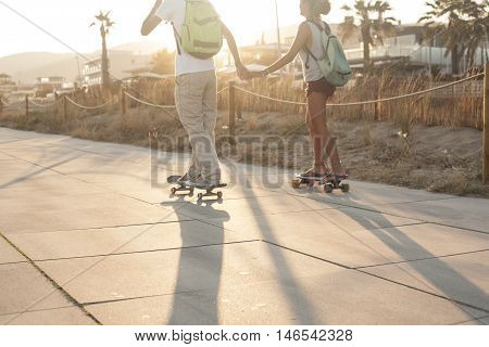Young couple skating together next to the beach