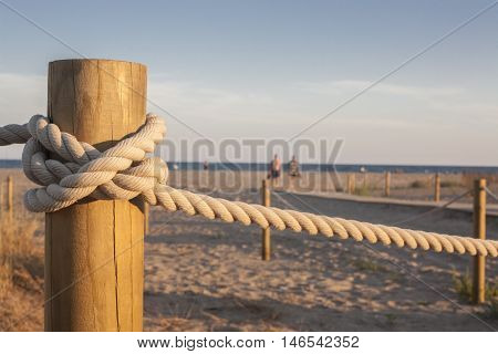 Wooden stakes with rope on the beach at sunset