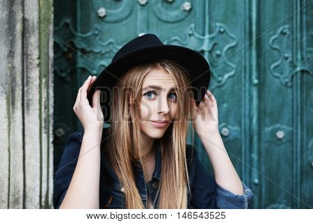 Close up portrait of beautiful playful smiling girl wearing stylish wide-brimmed black hat. Model looking at camera. City lifestile.