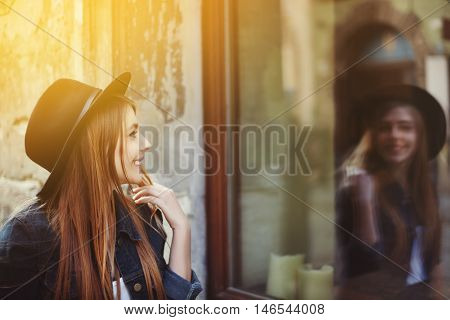 Portrait of young smiling woman looking at the shop window. Model wearing stylish wide-brimmed black hat. City lifestyle. Close up. Toned.