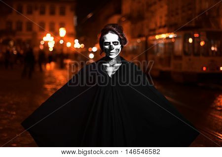 Young woman posing on the street in black costume with Halloween makeup . Waist up. Night city background.