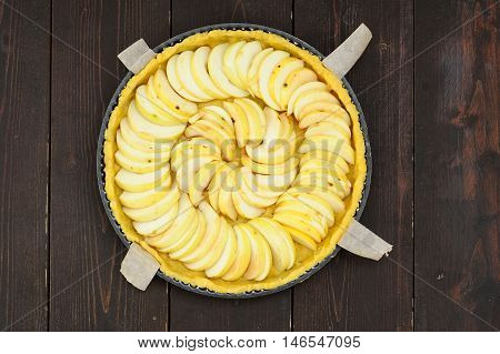 Apple tart unbaked overhead viewon dark wood background