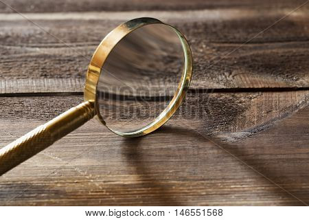 Gold magnifying glass with shadow on wooden background.