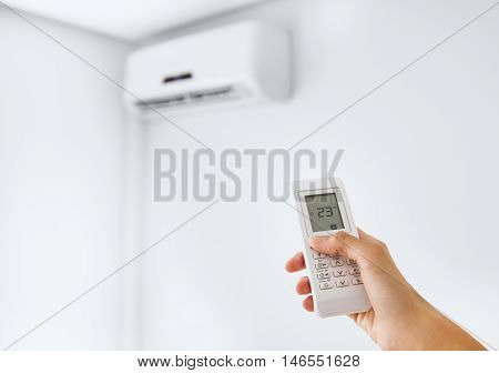 Hand holding remote control, adjusting temperature of air conditioning