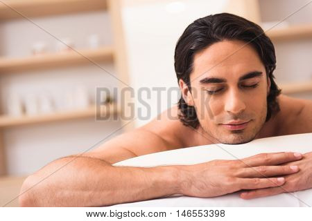 portrait view of a calm bristly man resting in spa center with closed eyes