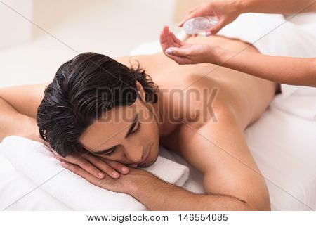Calm man is lying on massage table with relaxation. Masseuse hands preparing oil