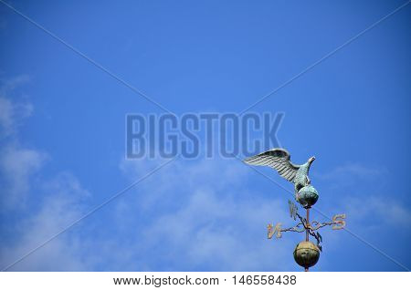 large eagle weather-vane set against a bright blue sky with a few puffy clouds
