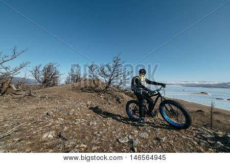 Fatbike (also called fat bike or fat-tire bike) - Cycling on large wheels. A cyclist sits on the bike on the ice. Against the background is Lake Baikal. The height of a hundred meters above sea level.