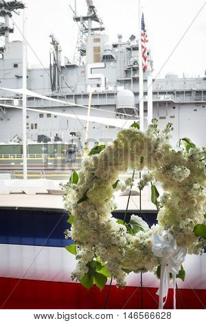 NEW YORK MAY 30 2016: Ceremonial wreaths at the Intrepid Sea Air & Space Museum for the Memorial Day Commemoration ceremony with USS Bataan (LHD 5) at Pier 88 in the background for Fleet Week NY 2016.