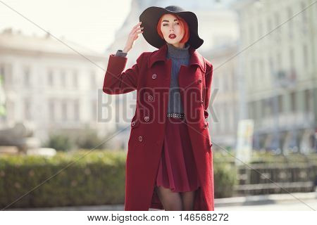 Portrait of young beautiful fashionable woman posing at street of the old city. Model wearing stylish black wide-brimmed hat, red coat. Girl looking at camera. Female fashion concept. Toned.