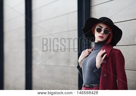 Closeup portrait of young beautiful fashionable woman with sunglasses. Lady posing on grey wooden background. Model wearing stylish wide-brimmed hat. Girl looking at camera. Female fashion. Copy space.