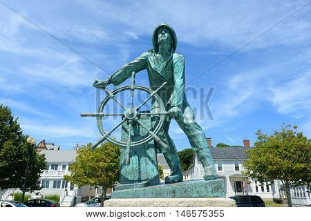 Gloucester Fisherman s Memorial a.k.a. Man at the Wheel located near the entrance of Gloucester, Massachusetts, USA. This statue was memorial cenotaph sculpture built in 1925 and now is the most famous landmark of Cape Ann.