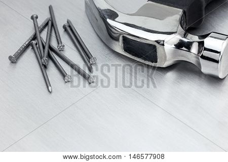 Scratched Metal Table Background With Nails And A Hammer On It