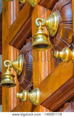 Golden bells on a wooden carving door of Hindu Temple