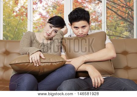 Two young bored couple sitting on the couch while holding pillow at home with autumn background on the window