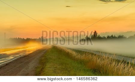 The road going near fields at sunset