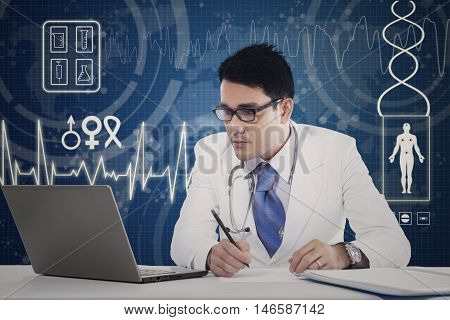 Male physician looking the laptop while writing a prescription with virtual screen background
