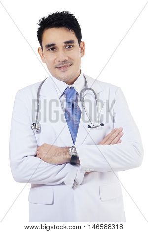 Photo of a young male general doctor standing in the studio while smiling at the camera and folded hands