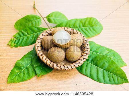 Fresh longan with longan leaf set on wooden table