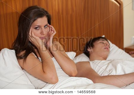 Unhappy Woman And Her Snoring Husband.