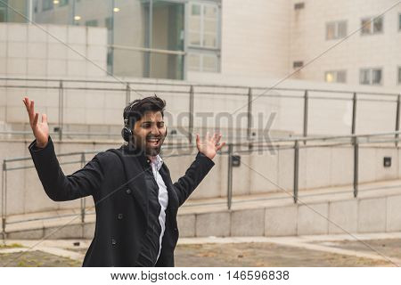 Handsome Indian Man Listening To Music In An Urban Context
