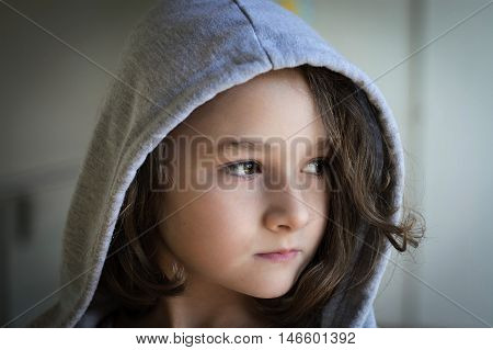 Cute little girl with hoodie posing wile looking through the window