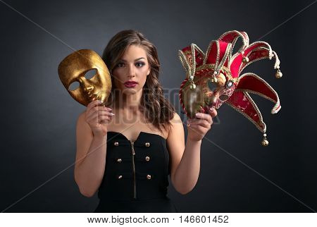 Beautiful woman in black dress with carnival mask