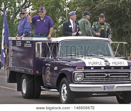 PHOENIX, AZ, USA - NOV. 11: Five male recipients of the Purple Heart riding on the back of a purple truck with the words Purple Heart painted on the hood in the Veteran's Day Parade in Phoenix, Arizona on November 11, 2011.