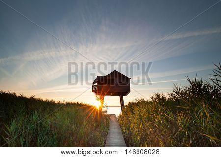 sunbeams behind wooden observation tower Nieuwe Statenzijl Netherlands
