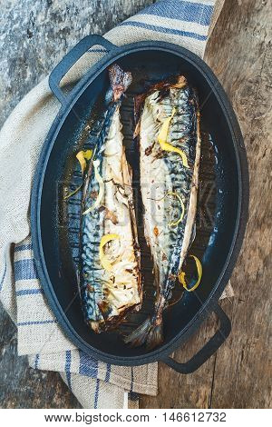 fish mackerel with a metal mold for baking on a towel and a wooden tableю
