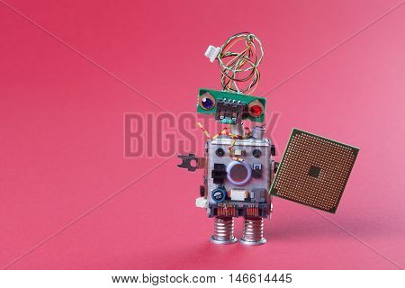 Robot with electronic chip board. vintage design toy mechanism with funny head, electrical wire hairstyle, colorful blue red eyes. Copy space, pink background