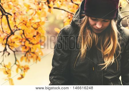 Sad Woman walking in park with autumn leaves on background outdoor Seasonal melancholy Lifestyle concept