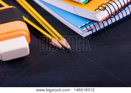 School Supplies Pencil, eraser, notebook on a dark background