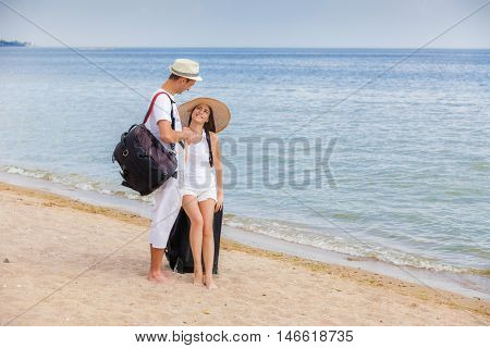 Young couple in love on the beach with travel bags