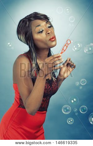 Pin up style fun image of an African Caribbean woman blowing bubbles