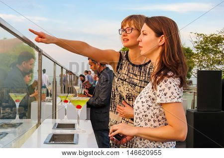 SINGAPORE, REPUBLIC OF SINGAPORE - JANUARY 08, 2014: Two girls consider Singapore from a rooftop of 1-Altitude Gallery and Bar, the highest alfresco bar in the world