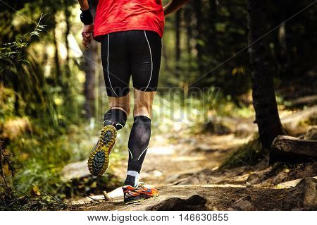 view back marathon runner running in woods. closeup of legs compression socks and sole of running shoes