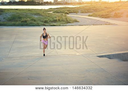 Athletic female long distance runner out jogging along a country road at dawn with a golden glow from the rising sun