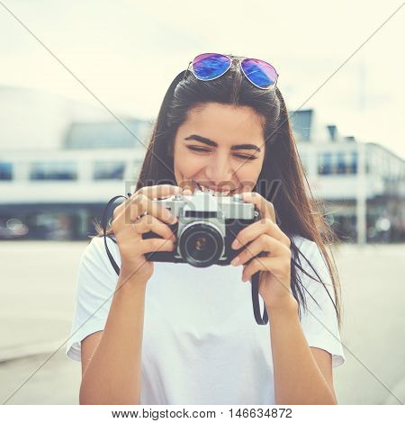 Laughing young woman checking the viewfinder on the back of her camera after taking an image in the center of town