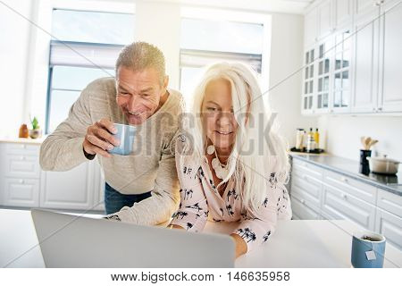 Adorable middle aged couple with happy expression looking at computer while drinking coffee in kitchen