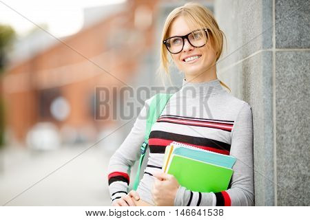 young student with books near wall of building