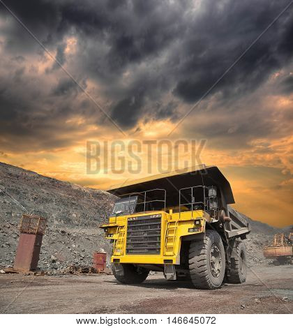 Mining truck loaded withiron ore driving along the opencast on stormy sunset