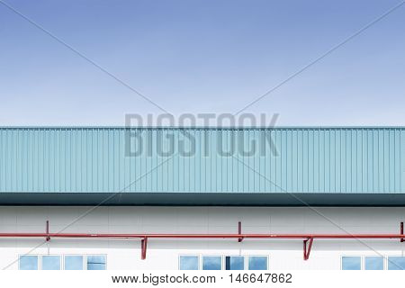 The side view of factory buildingwhich build from metal sheet.The red pipe line installed at the wall of factory building