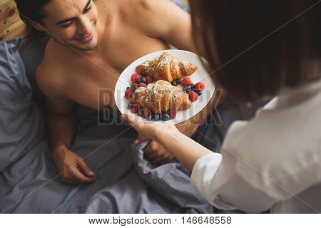 close up of a woman holding breakfast in front of a man
