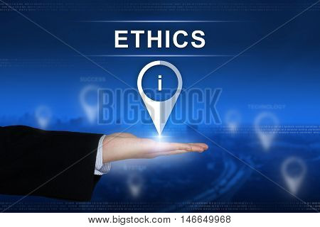 Ethics button with business hand on blurred background