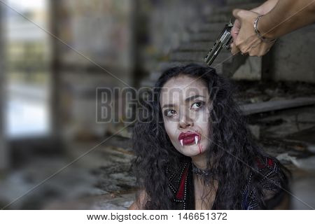 women hand sleeve pointing gun on vampire women head. A woman at gunpoint