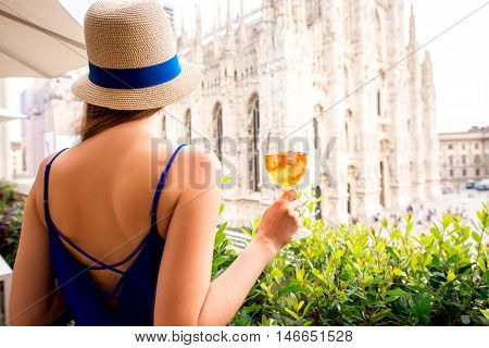 Young woman standing with traditional italian alcohol drink spritz aperol on the terrace with great view on Duomo cathedral in Milan