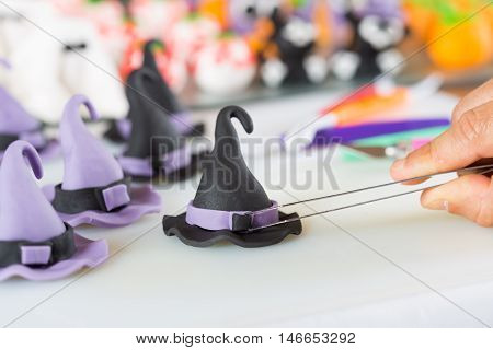 Confectioner working on the figures of Halloween with fondant paste