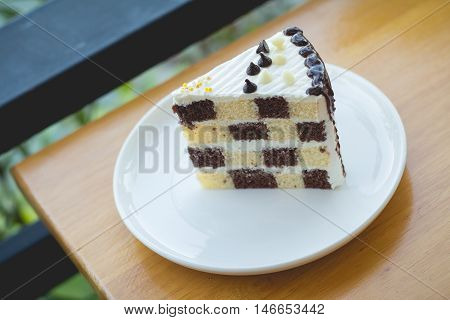 chocolate and butter sponge cake. Peace of sponge cake in cozy outdoor cafe.